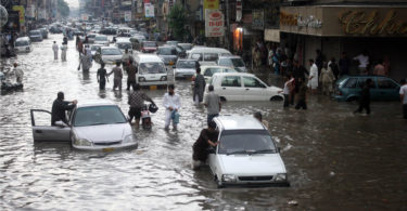 Pakistani commuters travel on a flooded street following a heavy rainfall in Karachi. via Shutterstock
